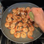 Squeezing lime over cooked shrimp in skillet for Garlic and Lime Shrimp with Tzatziki Sauce. The Shrimp is simply sauteed with minced garlic, olive oil, and lemon for big bold flavors. The Tzatziki Sauce is bright and cool with creamy yogurt with fresh cucumber, lime, garlic, and scallion. #shrimp #easydinner #dinner #seafoodrecipes #shrimprecipes