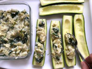 Stuffing zucchini halves for Spinach Artichoke Stuffed Zucchini. Each fantastic bite gives you creamy artichoke, nutty cheesy Parmesan, spinach, and zucchini. Prepare entirely ahead, then bake 20 minutes and enjoy! #vegetarian #zucchini #stuffedzuchini #spinach #artichoke #springrecipes #healthyfood #healthydinner #healthyrecipes #glutenfree