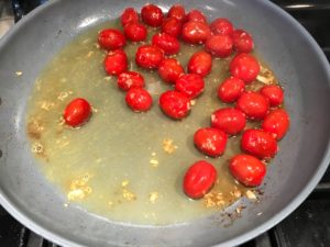 Grape or Cherry tomatoes cooking in skillet for Chicken and Cherry Tomato Pasta with basil and parmesan. It's easy and so delicious! #pasta #tomatoes #easydinner #dinner #easyrecipes #healthydinner #chicken