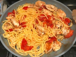 Chicken, Pasta, and Cherry tomatoes cooking in skillet for Chicken and Cherry Tomato Pasta with basil and parmesan. It's easy and so delicious! #pasta #tomatoes #easydinner #dinner #easyrecipes #healthydinner #chicken