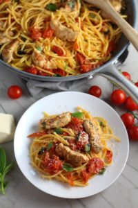 Chicken and Cherry Tomato Pasta with basil and parmesan on a plate with skillet in back. It's easy and so delicious! #pasta #tomatoes #easydinner #dinner #easyrecipes #healthydinner #chicken