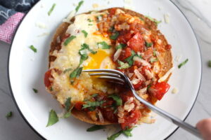 Skillet Eggs in Spicy Tomato Pepper Sauce with Manchego Cheese served over a crispy corn tortilla with skillet in back. With a smoky, spicy, thick, and luscious red pepper tomato sauce. #eggs #huevosrancheros #tomatosauce #easydinner #brunch #shakshuka