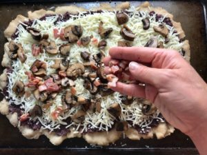 Hand putting pancetta and mushrooms on cheese on flatbread for Olive & Pancetta Flatbread with mozzarella, mushrooms, and fresh basil. #flatbread #pizza #olives #tapenade #mediterranean #easydinner #dinner