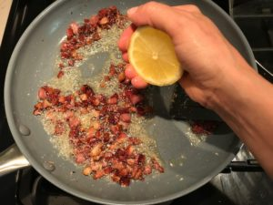 Hand squeezing half a lemon over cooked diced Pancetta in skillet for Pancetta, Parmesan, and Pepper Pasta. The Pancetta gives a salty and slightly peppery flavor, Parmesan cheese creates a nutty and creamy sauce, and the ground black pepper gives a peppery flavor that makes this pasta stand out. #pasta #easypasta #easydinner #dinner #italian #familydinner #onpotdinners #onepandinners #parmesan