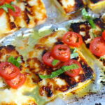 Grilled Halloumi Cheese & Tomato Salad on pan. It's insanely delicious! Grilled Halloumi has a strong savory and salty flavor that is slightly creamy and incredibly addictive. Paired with my simple Tomato and Basil salad, each bite is simply heaven. #halloumi #appetizers #salads #grilling #summerfood