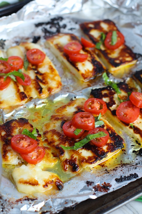 Grilled Halloumi Cheese & Tomato Salad is insanely delicious!  Grilled Halloumi has a strong savory and salty flavor that is slightly creamy and incredibly addictive.  Paired with my simple Tomato and Basil salad, each bite is simply heaven. #halloumi #appetizers #salads #grilling #summerfood