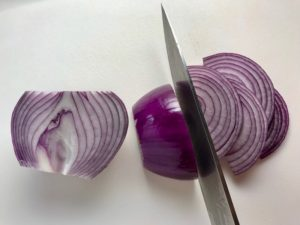 Knife cutting red onion into slices for Pickled Onions in a bowl soaking. They are tart, tangy, sweet, and savory.  They go on just about anything and are so unbelievably delicious, they can make a shoe taste good!  Best part, you can make a ton of them ahead!