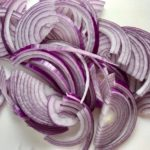 Slices of red onion for Pickled Onions in a bowl soaking. They are tart, tangy, sweet, and savory. They go on just about anything and are so unbelievably delicious, they can make a shoe taste good! Best part, you can make a ton of them ahead!