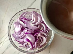 Slices of red onion in bowl with vinegar about to be poured over top for Pickled Onions in a bowl soaking. They are tart, tangy, sweet, and savory.  They go on just about anything and are so unbelievably delicious, they can make a shoe taste good!  Best part, you can make a ton of them ahead!