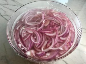 Slices of red onion with pickling liquid in bowl covered for Pickled Onions in a bowl soaking. They are tart, tangy, sweet, and savory. They go on just about anything and are so unbelievably delicious, they can make a shoe taste good! Best part, you can make a ton of them ahead!